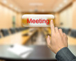 Male hand pressing meeting button on meeting room