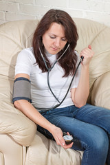 girl sits on a soft armchair checking blood pressure