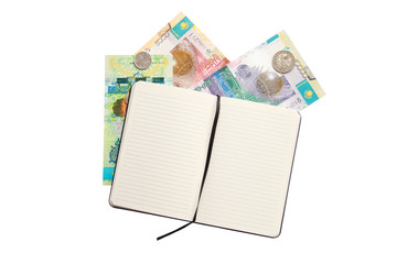 opened notebook and some money of kazakhstan over white