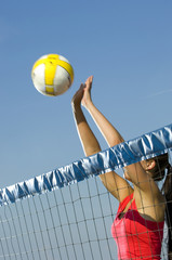Young woman playing Beach Volleyball in summer