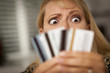 Upset Woman Glaring At Her Many Credit Cards