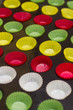 Постер, плакат: Vibrant cupcake wrappers backing cups in siliconmetal tray