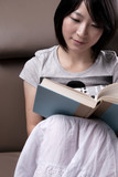 Young woman sitting on sofa reading book