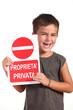 bambino sorridente mostra cartello proprietà privata