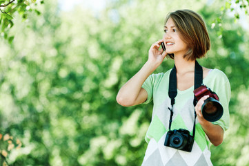 young woman talking phone holds camera