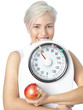 Girl with apple and scales is happy about ideal body weight
