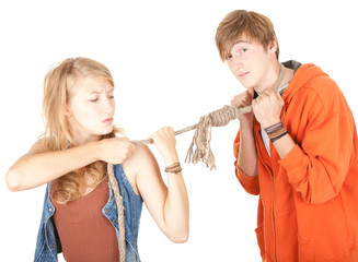 couple conflict - young woman pulling man on the rope