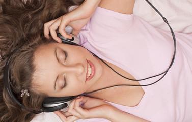 Юная девушка слушает музыку в наушниках