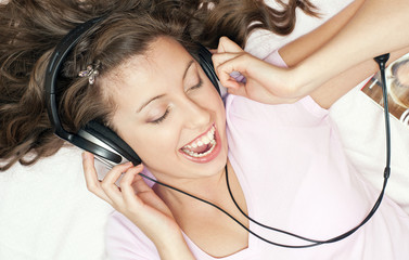 Радостная девушка слушает музыку в наушниках