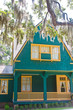 Yellow Trim on Green Home Under Spanish Moss
