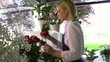 Girl at work in flowers shop and smelling red roses