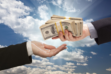 Handing Over Cash with Dramatic Clouds and Sky