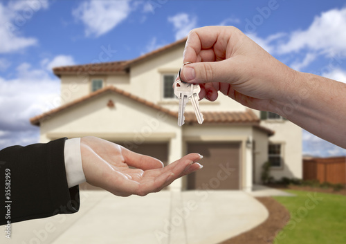 Handing Over the House Keys in Front of New Home