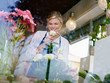 Blonde girl working in flowers shop with roses and gerbera