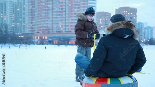 Young boy starts pulling sled with other boy
