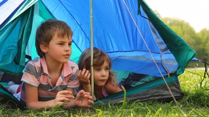 Boy with girl lay peeping out of tent