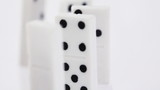Dominoes with black dots stand vertically and pass consistently