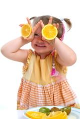 Ein Kind haltet Orangenscheiben vor die Augen/ V