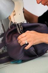 Closeup on woman sewing leather handbag