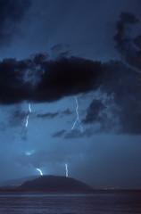Lightning strike over small island at sea