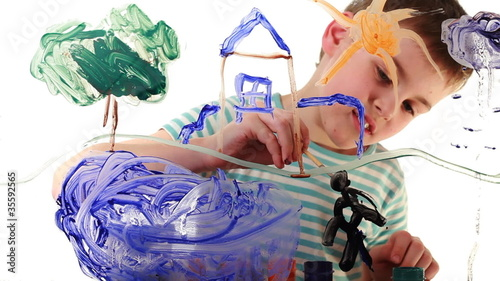 Boy draws picture of colored paint on transparent glass