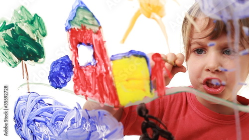 Little girl paint himself at home in picture on glass