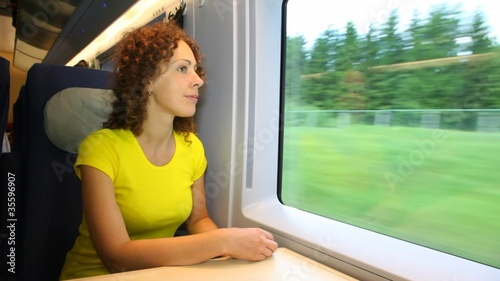 Woman sits and smiling in train near window during movement