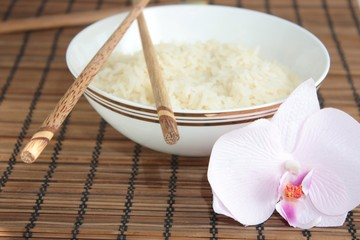 Bowl of rice and chopsticks with an orchid