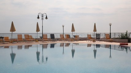 Water pool against chaise lounges and beach umbrellas