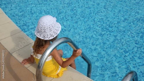 Girl sits on border of pool and douses her feet in water