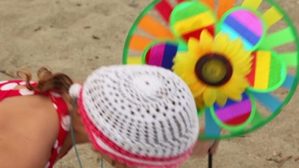 Toy with sunflower in center is set in ground, then girl took it