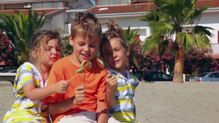 Three kids sitting on sand and showing lolly candy to each other
