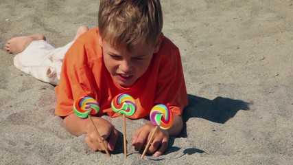 boy lying on the sand, in front of him three candy