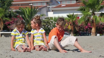 Tree kids sitting on sand