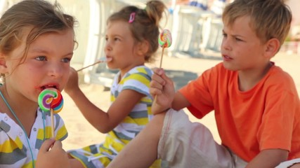 Three kids eating lolly candy sitting on sand
