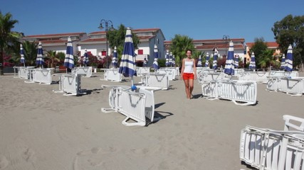 Woman walking closer by sand between lot of deckchairs
