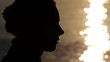 Silhouette of woman head with sunshine reflected in water behind