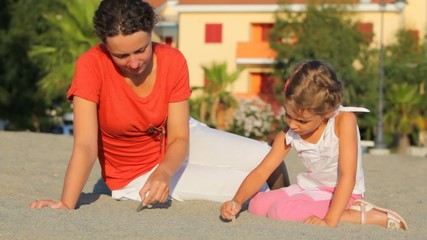 Mother and daughter sitting on sand and drawing on it