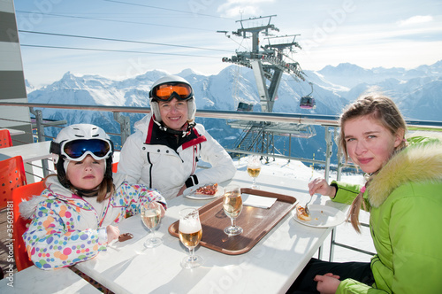 Skiers enjoying lunch in winter mountains