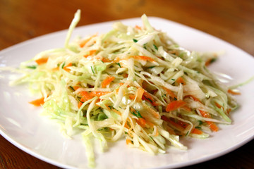 fresh coleslaw salad served on white plate