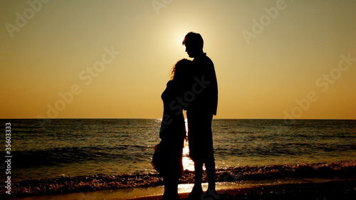 Girl and boy stand on seashore, silhouettes at sunset, part3