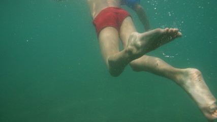 Boy swims in sea to shore, then camera shoots him under water