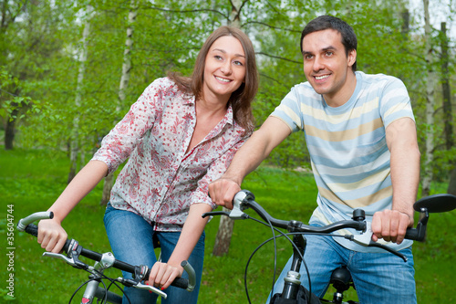 Happy young couple riding bicycles