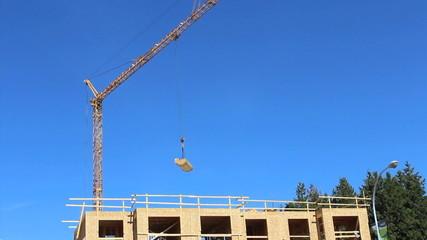 Constuction Crane Carrying Lumber