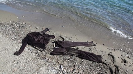 Brown suit lay on sand near sea water