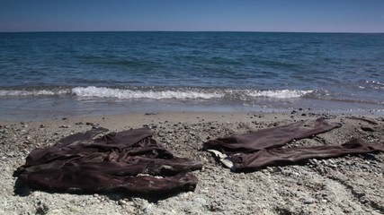 Brown suit lay on sand near water