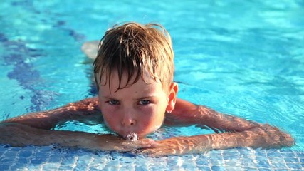 Boy clings to the edge of the pool