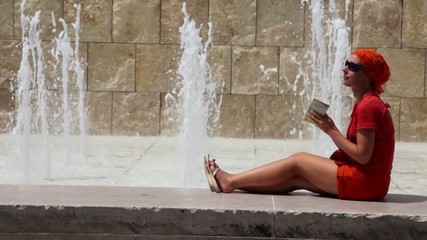 Woman sits on the edge of fountain and watch  map