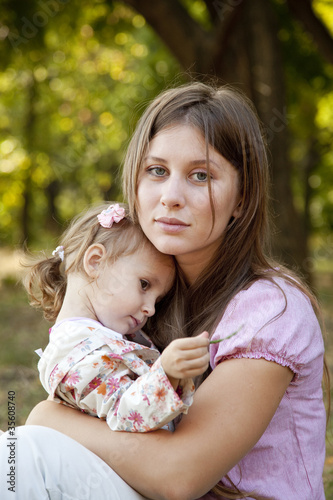 Sad little girl and mother in the park