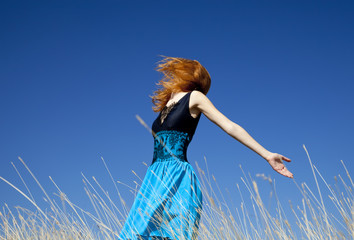 Redhead girl at windy field.